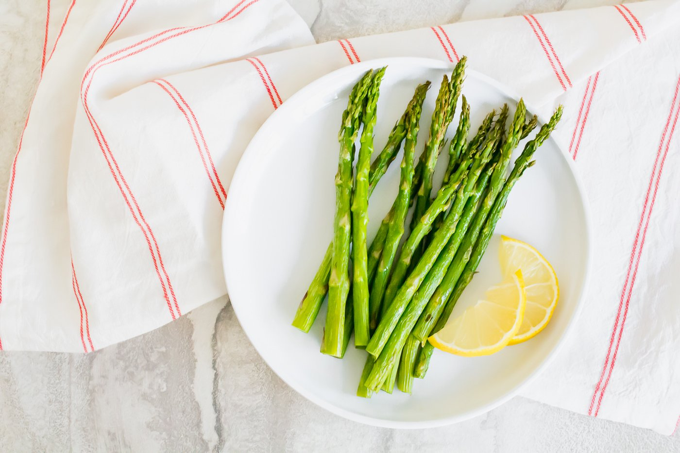 overhead shot of cooked asparagus on a white plate on top of a white and red striped napkin