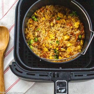 Multiple servings of fried rice in a black air fryer with a wooden spoon to the left