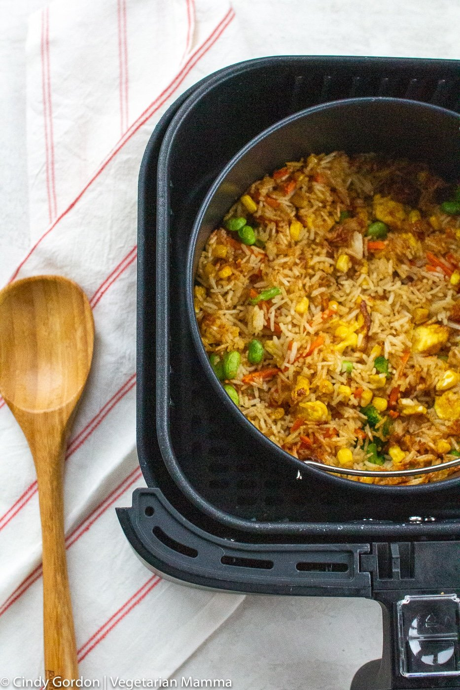 Air Fryer Fried Rice in air fryer basket with wooden spoon on the left