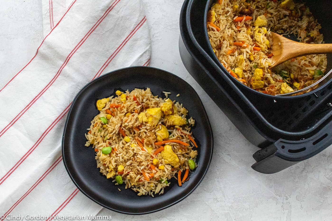 Air Fryer Fried Rice served on a black plate next to more rice in the air fryer basket