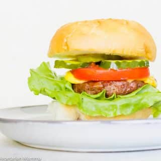 air fryer hamburger on a white plate with a white background