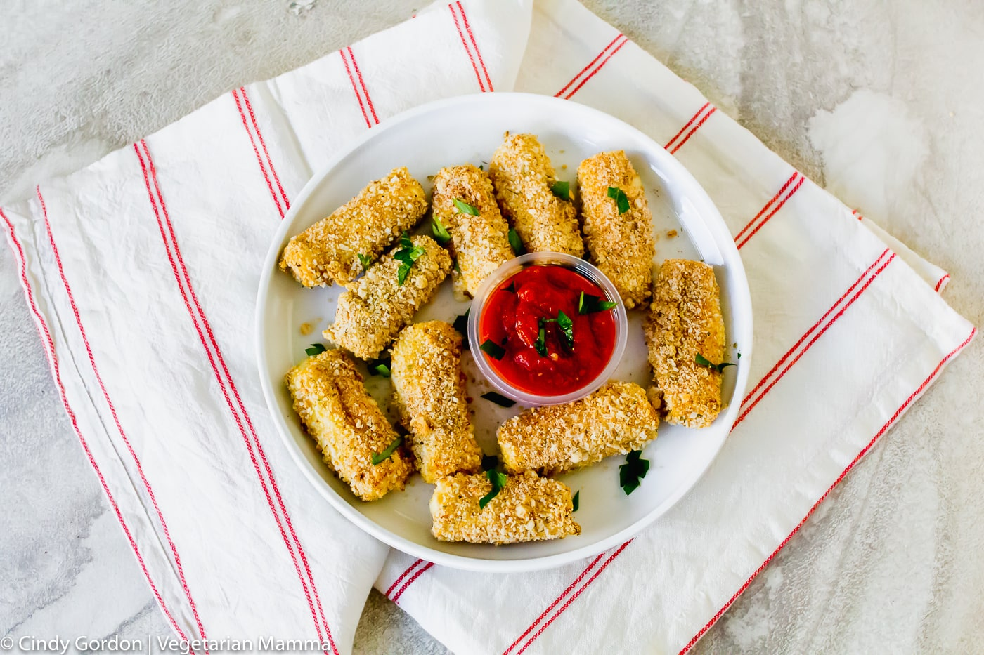 overhead shot of air fryer mozzarella sticks on a white plate and white background