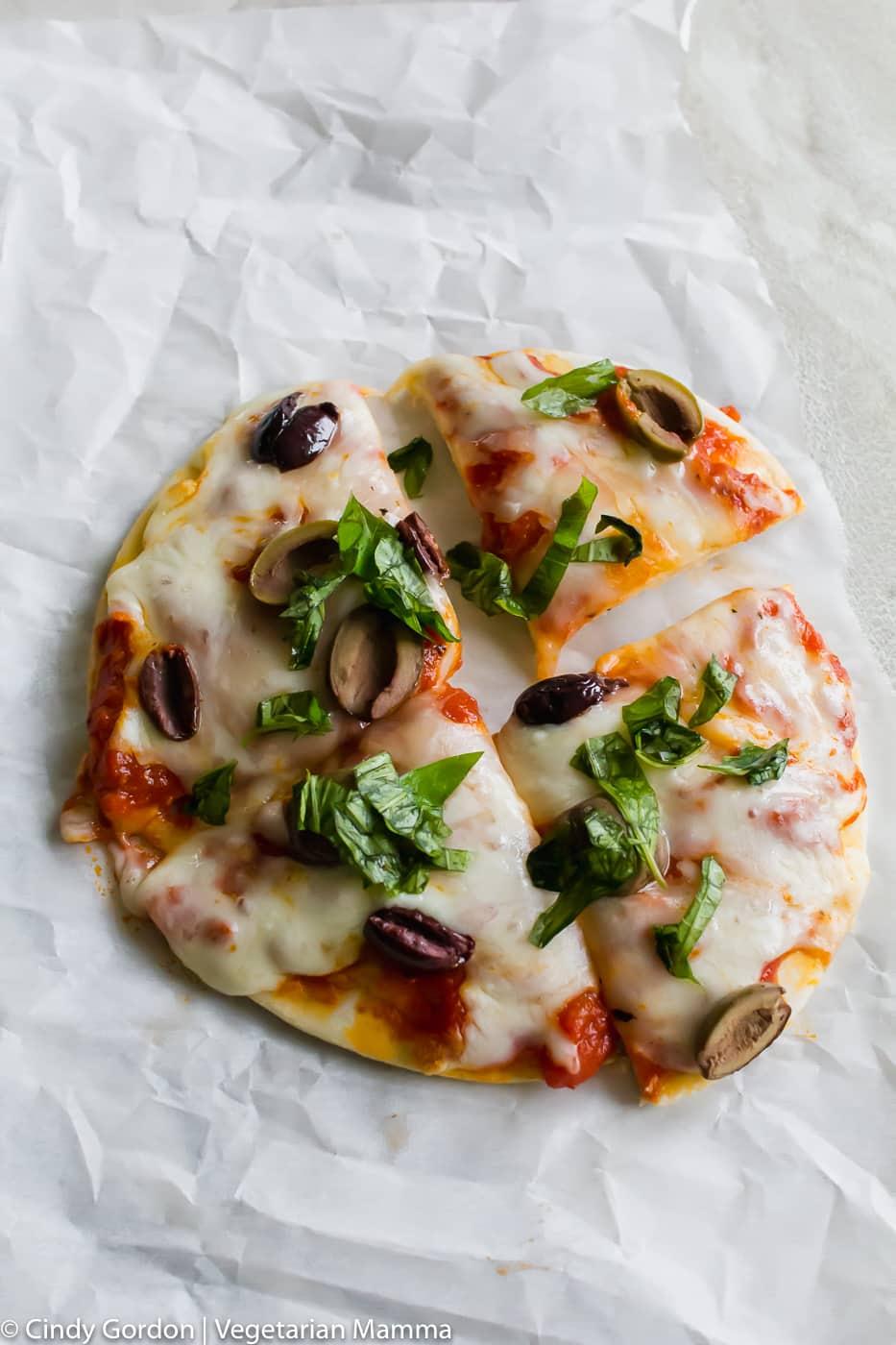 Pizza cut into four pieces on white parchment paper
