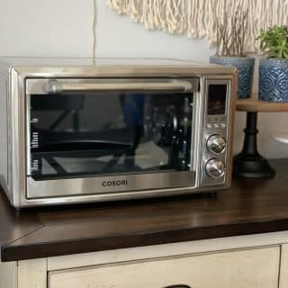 Cosori Air Fryer Oeven on top of wooden buffet
