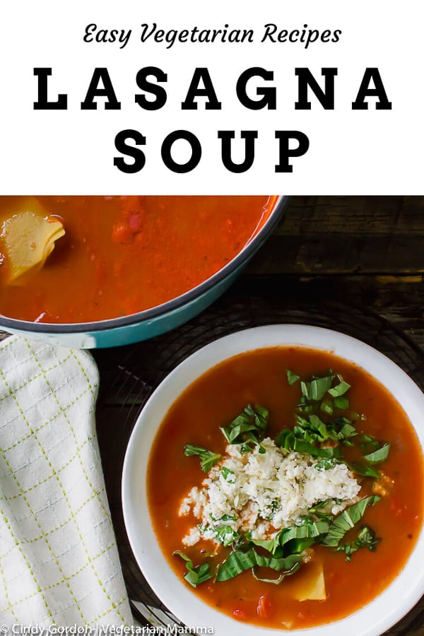 lasagna soup in a white bowl with cheese and green herbs on top