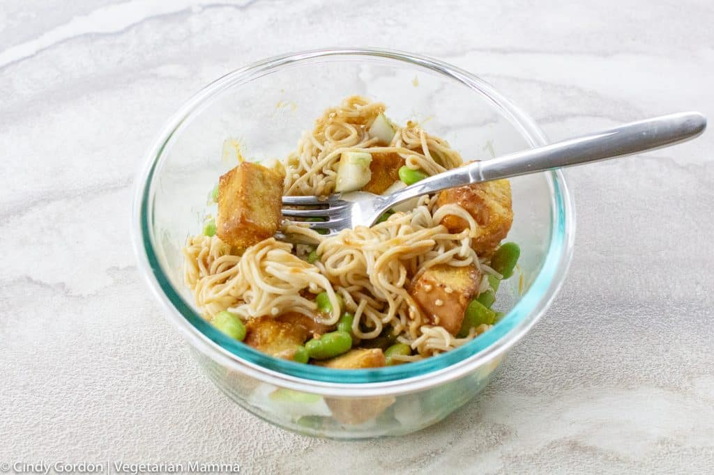 Tofu noodle bowl mixed together served in a glass circle bowl on a white background