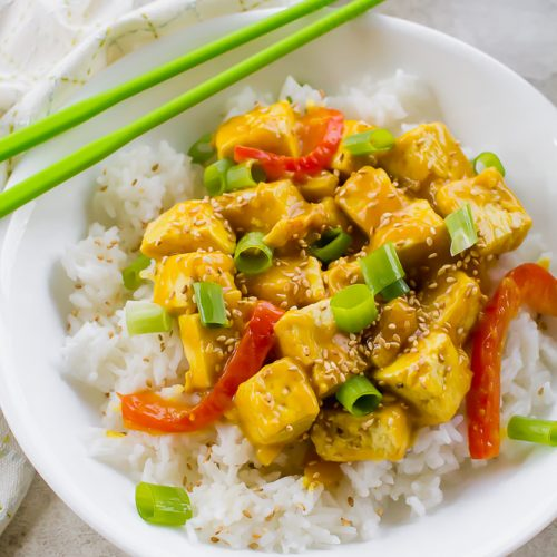 orange tofu in a white bowl on a white background tabletop with green chopsticks