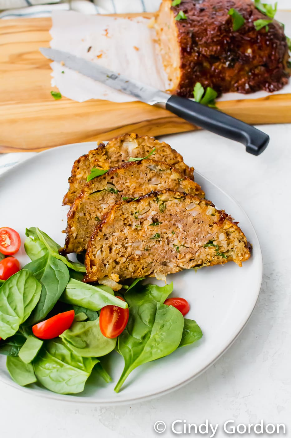 Air Fryer Meat Loaf sliced on a white plate with remaining loaf in the background. Served with green spinach and red tomatoes