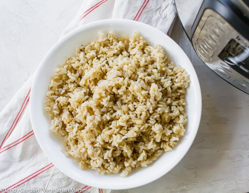cooked brown rice in a white bowl on a striped red and white towel