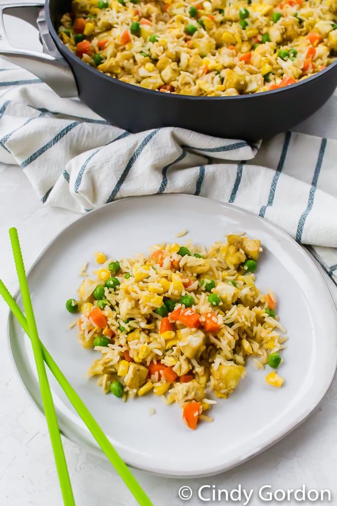 fried rice with carrots, peas, corn, and tofu on a white plate with chopsticks