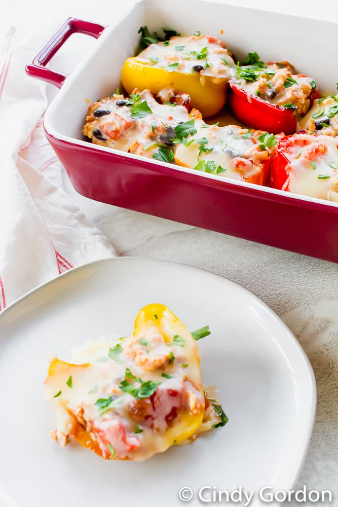 Image of a yellow stuffed bell peppers with melted mozzarella cheese on a white plate. red baking dish with other peppers in background