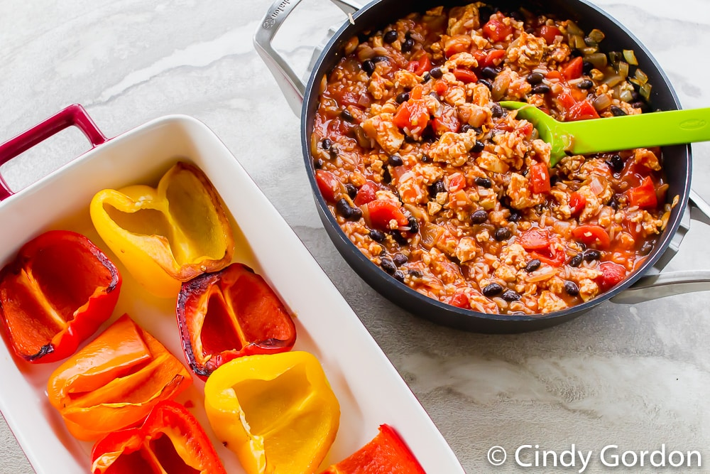overhead shot of bell pepper halves in baking dish, unstuffed. Stuffing mixture in black skillet next to baking dish.