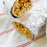 two burritos with rice and vegetables wrapped in foil