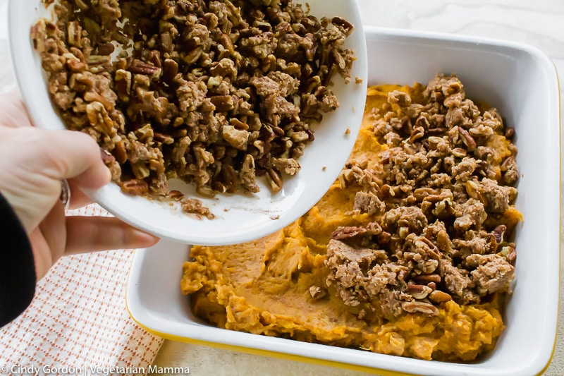a hand pouring a bowl of pecan topping over a dish of sweet potato casserole