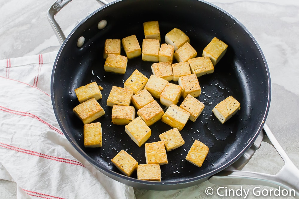picture of golden tofu chunks in black skillet on a white counter