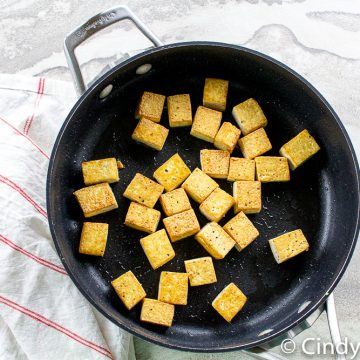 black skillet with golden crisp pan fried tofu with some oil