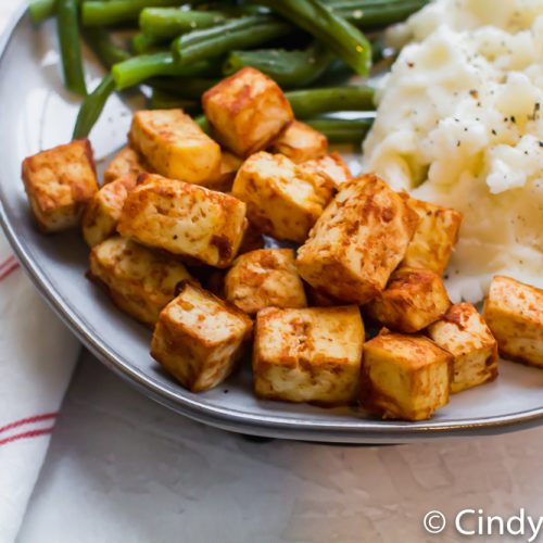 tofu dressed in barbecue sauce on a plate with rice and green beans