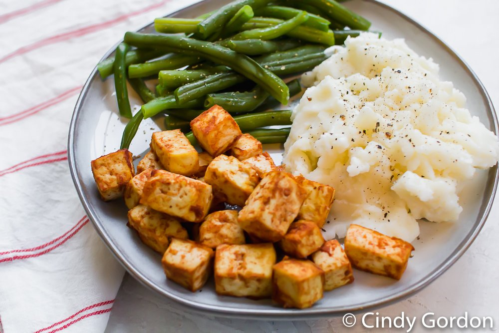 barbecue tofu squares on a plate with mashed potatoes and green beans