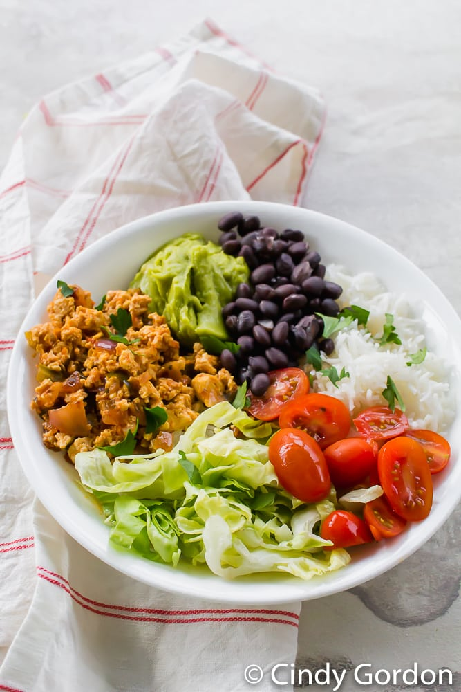 sofritas in a white bowl with rice, black beans, lettuce, tomatoes, guacamole, and cilantro