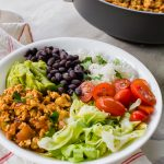 sofritas, lettuce, tomatoes, rice, black beans, and guacamole in a white bowl