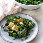 Tofu, kale, apples, green onions, and cranberries on a white plate