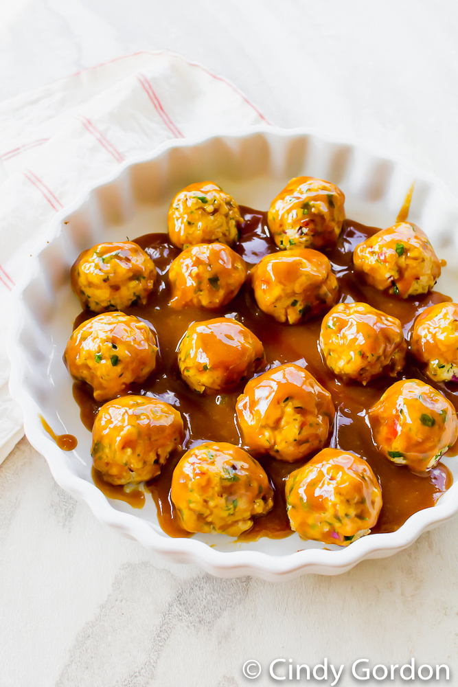 Tofu meatballs in a round baking dish glazed with brown sugar, ketchup, and dijon mustard