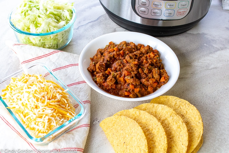 A white bowl of vegetarian taco meat is surrounded by cheese, lettuce, and taco shells