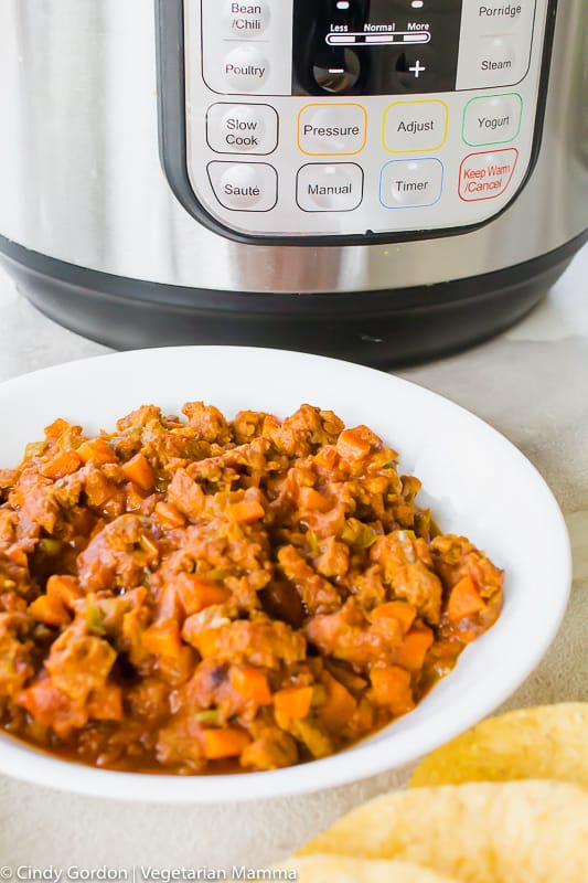 """A white bowl of vegetarian taco """"meat"""" in front of an Instant Pot"""