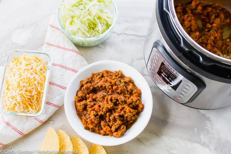 Taco meat in an Instant Pot and in a white bowl with taco toppings