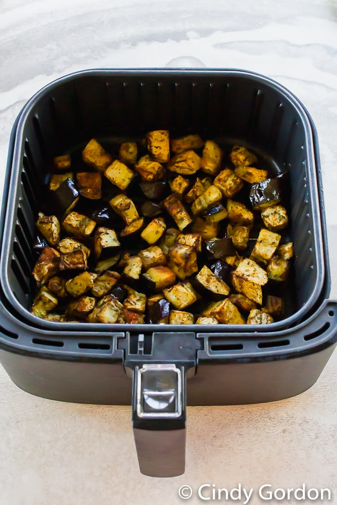 vertical photo of black air fryer basket with cooked eggplant cubes in it