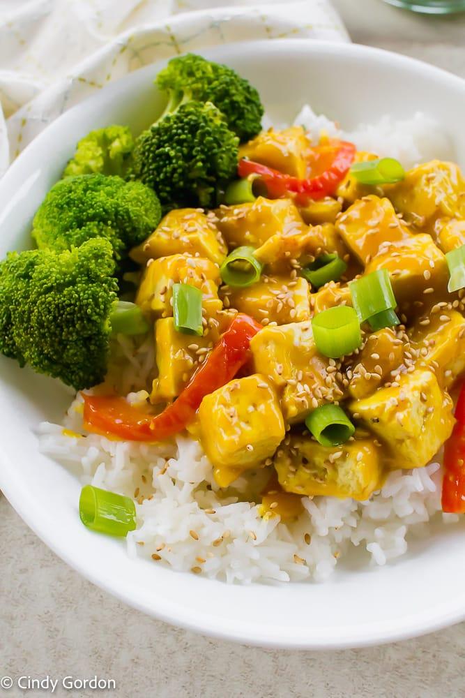 orange tofu in a white bowl with bright green broccoli