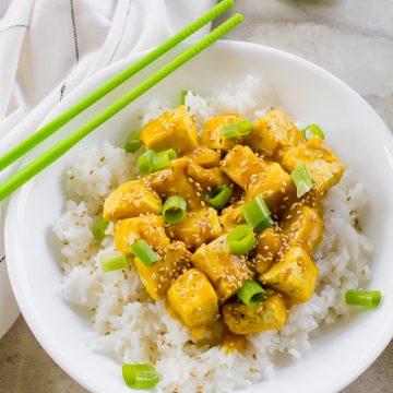 Vegan orange chicken in a white bowl with green chopsticks