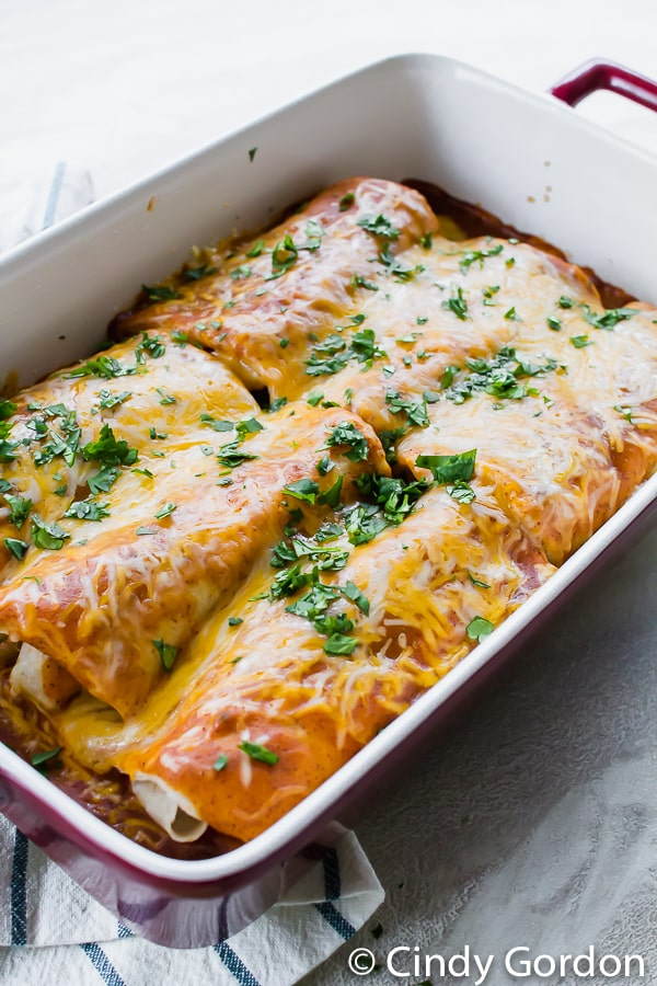 A red and white baking dish with enchiladas topped with cheese and cilantro