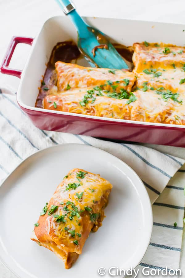 An enchilada on a round, white plate in front of a baking dish of enchiladas