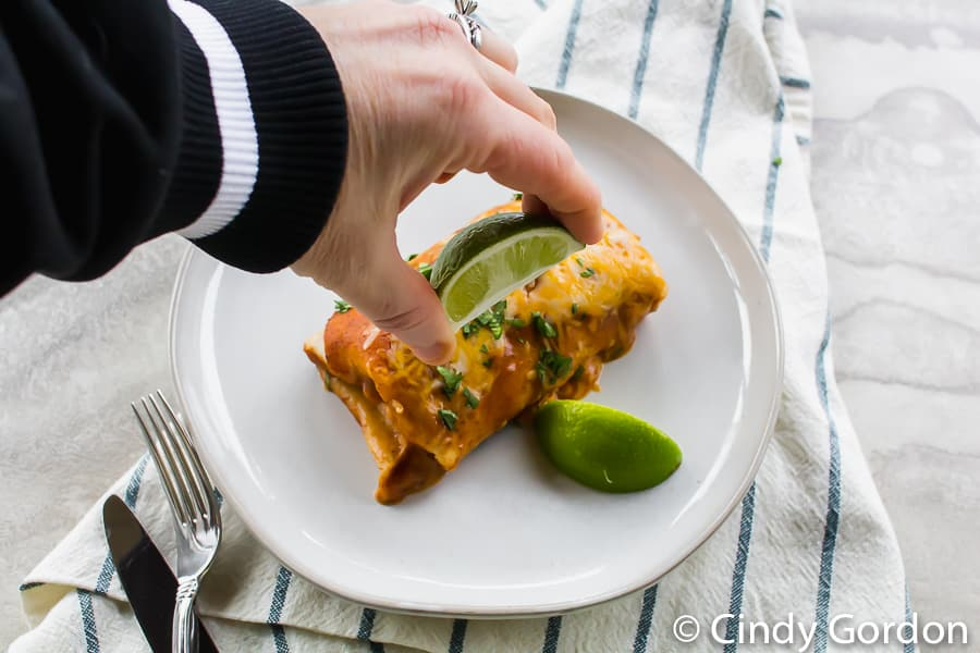Someone squeezing lime juice onto a vegetarian enchilada on a white plate