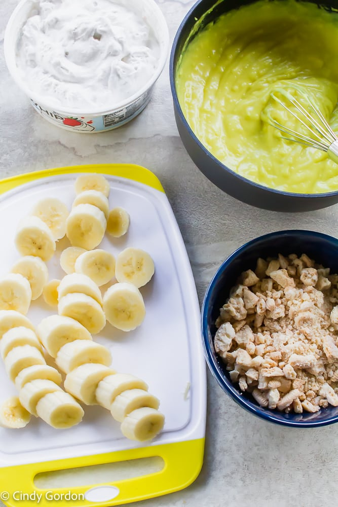 ingredients for dairy free banana pudding displayed, sliced bananas whipped cream crumbled cookies pudding