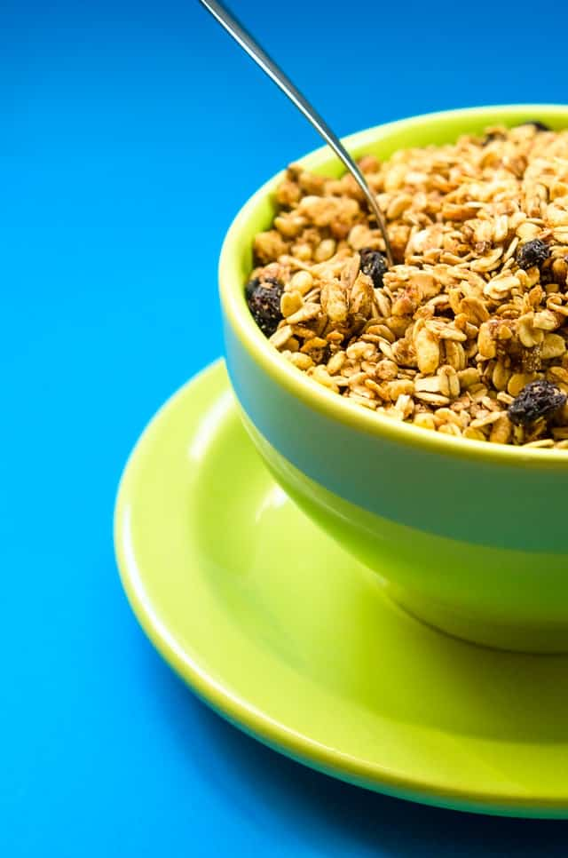 blue back ground with lime green bowl and saucer with raisin bran type of cereal inside with a silver spoon