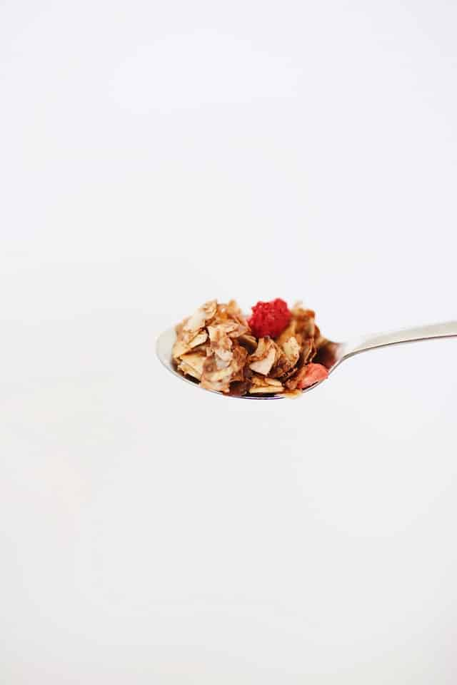 vertical photo with a white back ground. silver spoon with brown cereal and red berries on it