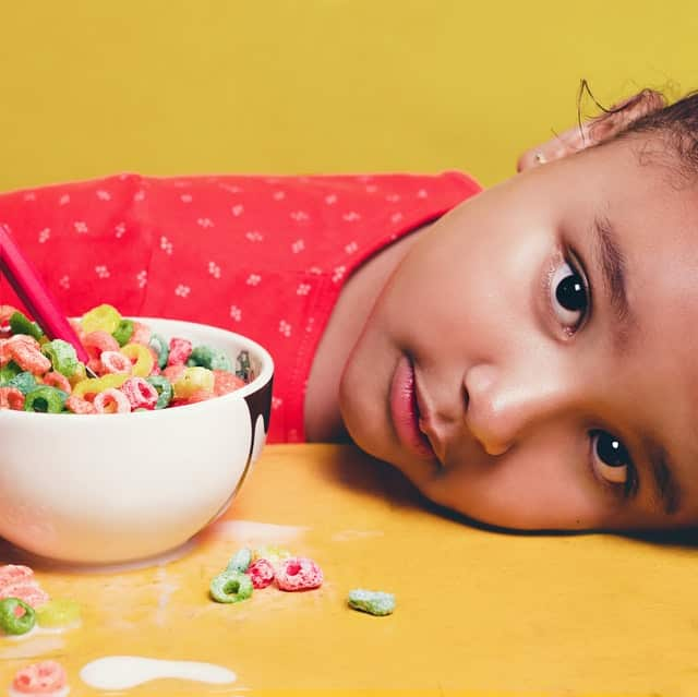 yellow back ground, girl in red shirt with little dots laying her head on the table looking at the camerea with a white cereal bowl of brightly colored cereal in it with a spoon, some milk and cereal have spilled on the table.