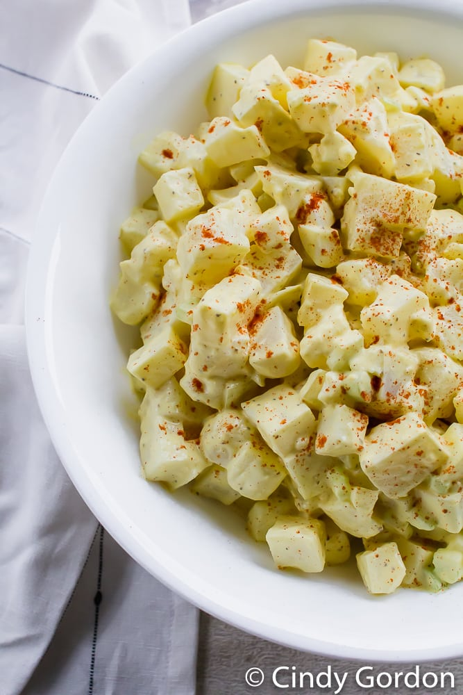 Close-up top shot of creamy potato salad in a white bowl with paprika