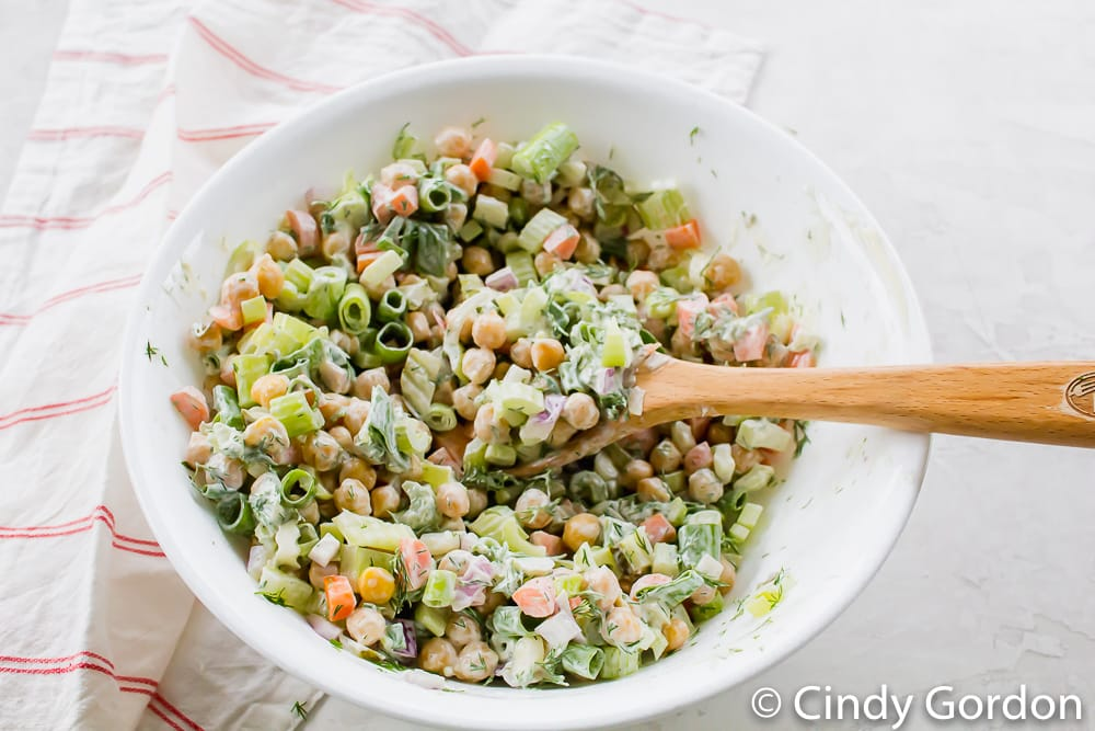 A white mixing bowl with chickpeas, carrots, celery, scallions, and a wooden spoon