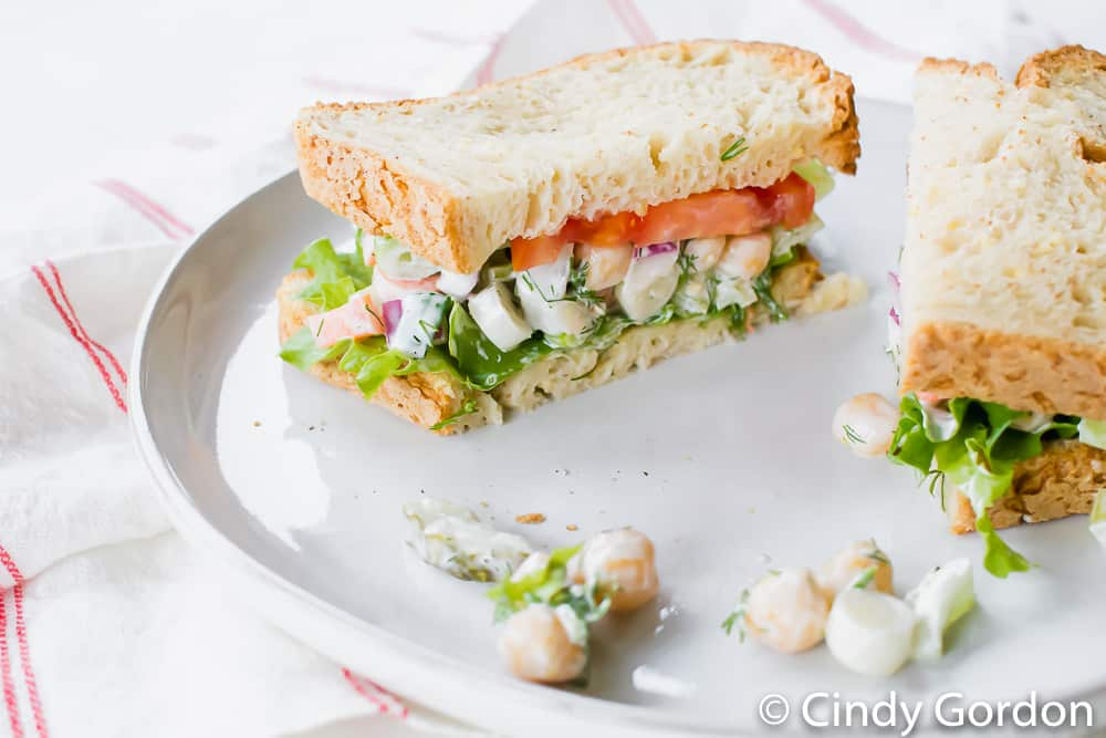 A vegan chickpea salad sandwich with lettuce and tomato on a white plate