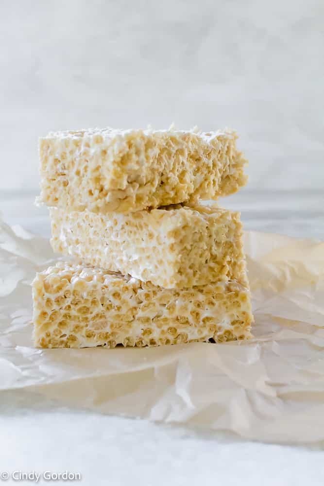 A stack of three vegan rice krispie treats on parchment paper