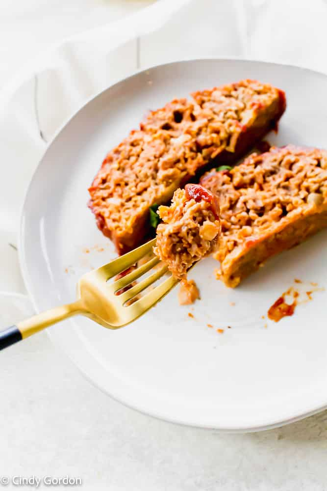 A bite of vegan meatloaf on a gold and black fork over a white plate of meatloaf