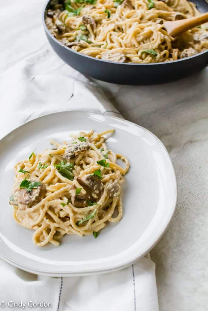 A white round plate of vegan carbonara with mushrooms next to a skillet of noodles