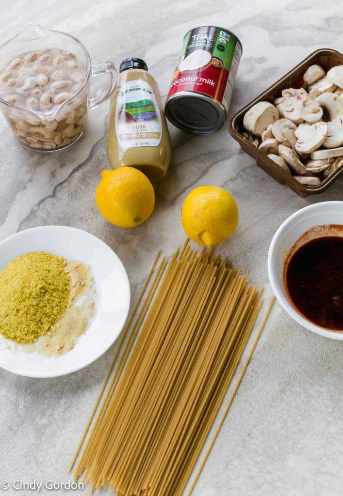 Sliced mushrooms, dry spaghetti, lemons, Dijon mustard, a can of coconut milk, soaking raw cashews and a plate of seasonings