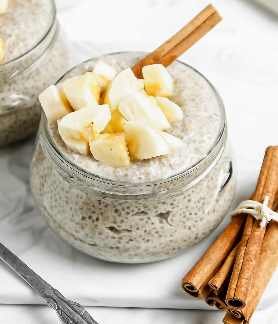 Banana chia seed pudding topped with fresh bananas and a cinnamon stick in a glass jar