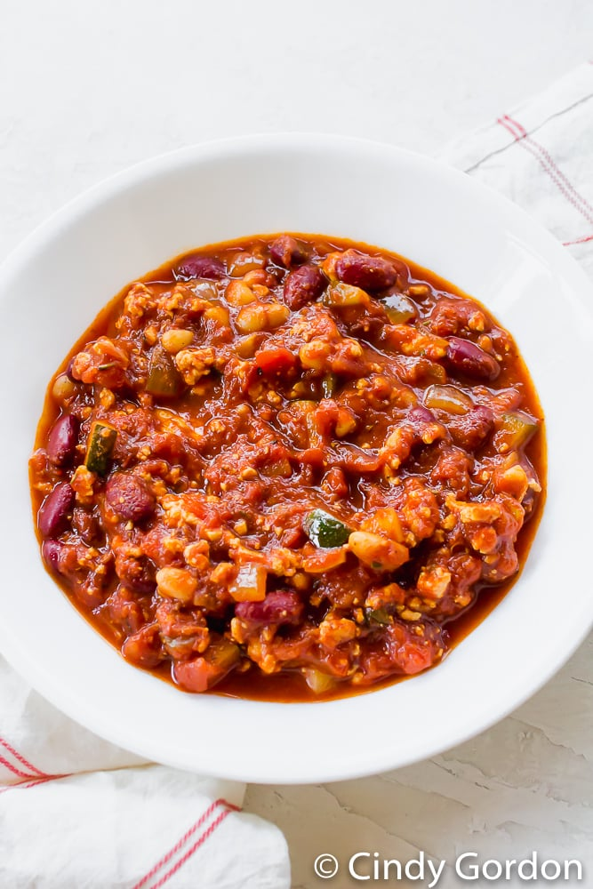 A hearty bowl of vegan chili with beans, zucchini, tomatoes, and tofu in a round white bowl