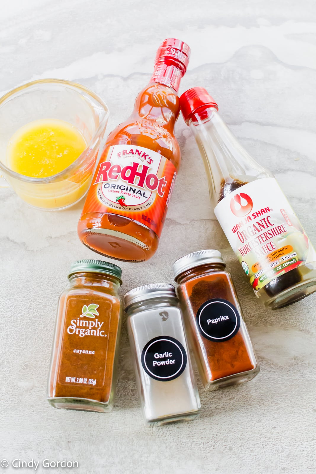 Bottles of hot sauce, vegan Worcestershire sauce, and seasonings with a measuring cup of melted butter