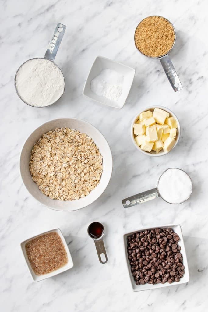 Bowls of butter, rolled oats, sugar, flour, baking soda, brown sugar, and chocolate chips on a granite countertop